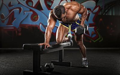 Man performs 3-point row with dumbbell to gain muscle