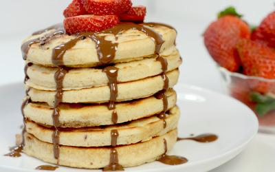 Tall stack of protein pancakes with melted chocolate and strawberries