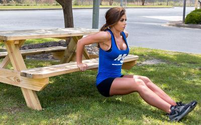 Fitness women doing chest dip workout outside on park bench