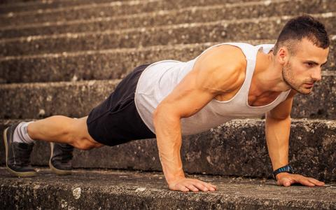 Fit muscular man doing push ups outside
