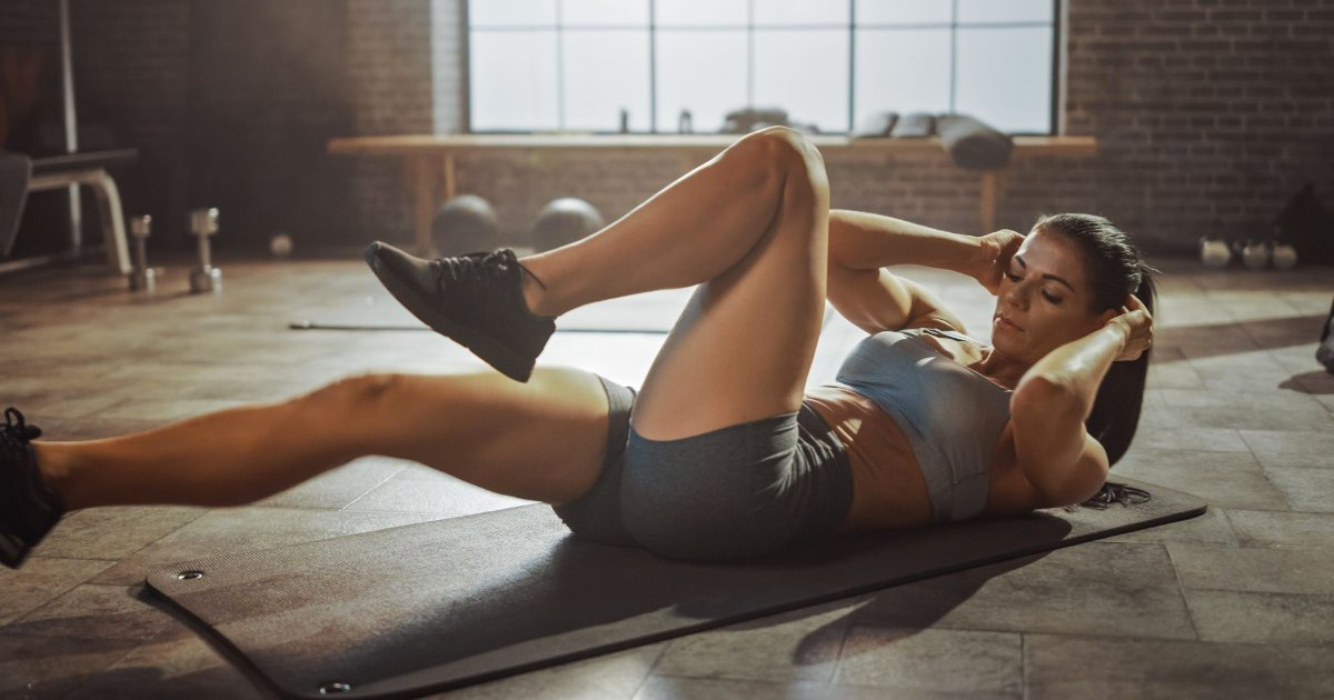 Woman doing crunches on an ab mat in a gym.