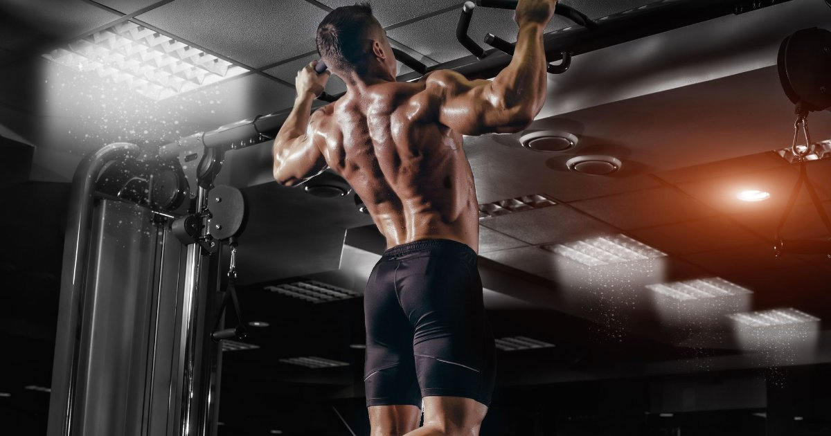 Muscular man in black shorts performing pull-ups in gym