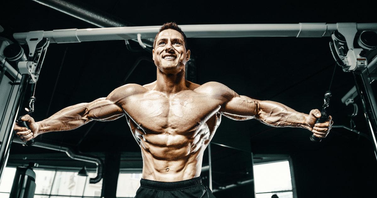 Shirtless, muscular man doing machine cable flys.