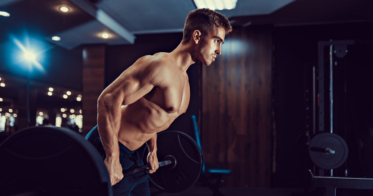 Muscular man doing barbell rows in gym setting.