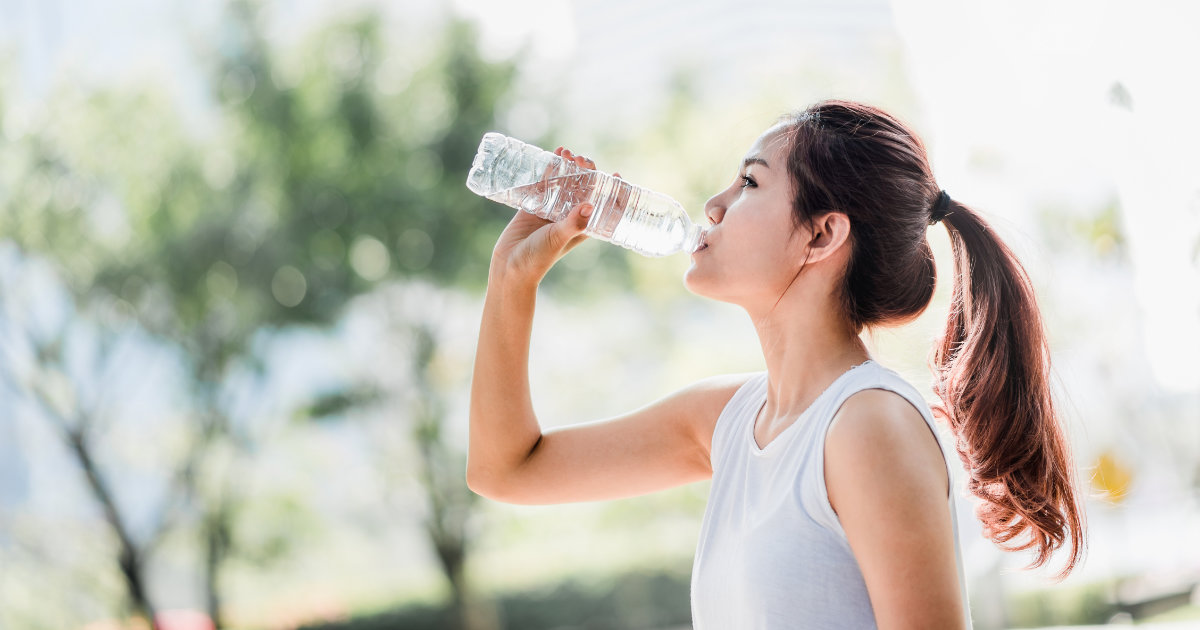 Woman drinking water outdoors.